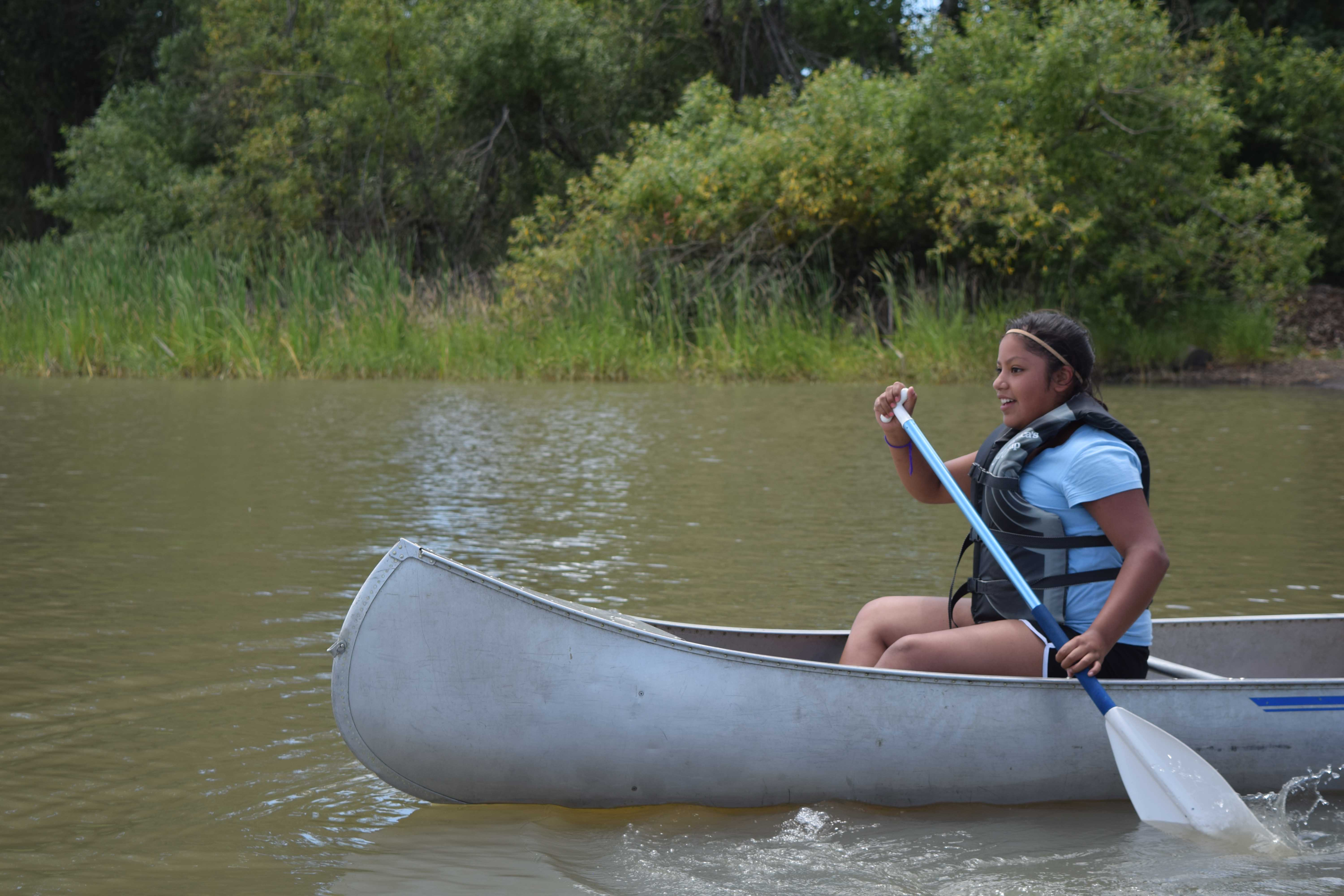 Confirmation Campers explore the reedy waters of Triangle Lake in canoes.